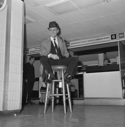 Comedian Dickie Henderson uses a stool as a prop while he waits for his plane at London Airport.