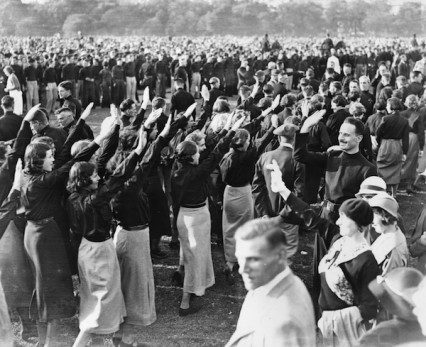 9th September 1934:  Sir Oswald Mosley acknowledging fascist salutes from female members of the British Union of Fascists at an evening demonstration in Hyde Park.