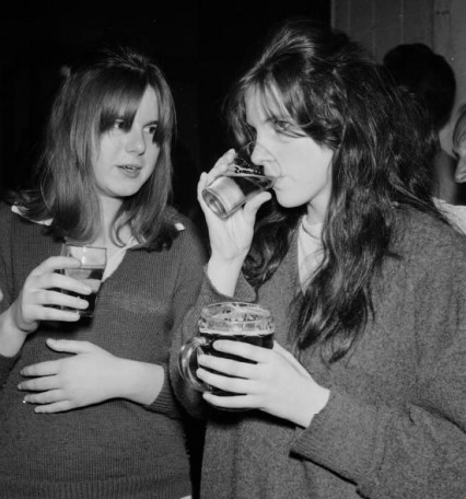 Two girls called Marian Dawson and Kathleen Mayo, the original caption makes sure that we know that Kathleen is holding her boyfriend's drink while they are drinking apple juice.