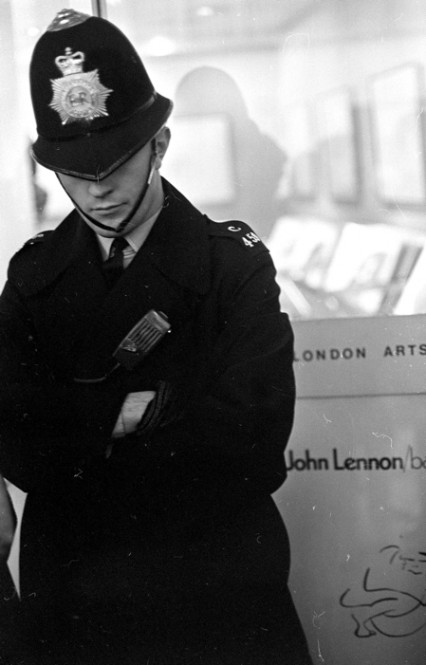 A police at duty outside Lennon's Bag One exhibition at London Arts gallery 1970