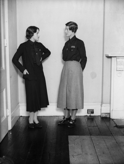 November 1933:  Mrs Swire a leading figure in the women's section of the British Union of Fascists wears the new uniform of grey skirt with black shirt talks to a member of the HQ staff in London who wear all black. Mosley was afraid the women members might jokily be called the 'black skirts'.